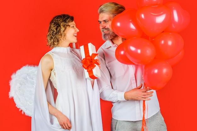 Urocza para w walentynki, anioł kupidyna z prezentami i balonami, para w walentynki.