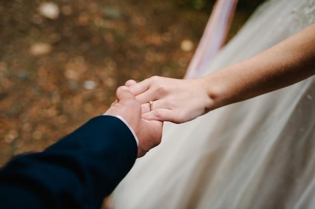 Urocza para zakochanych trzyma się za ręce. stylowa obrączka ślubna. wniosek. zaręczynowy. państwo młodzi w małżeństwie.