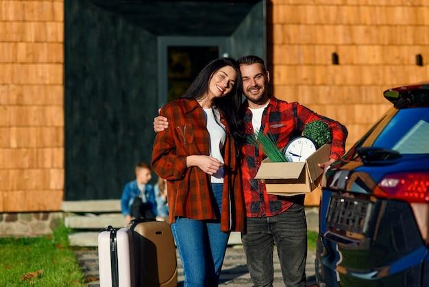 Urocza para zakochanych uśmiecha się i czuje szczęście, stojąc w pobliżu nowoczesnego domu z kartonowym pudełkiem z zegarem i zielonymi roślinami podczas przeprowadzki do nowego domu.