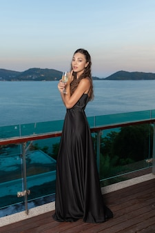 Urocza piękna dziewczyna pozuje w czekoladowej sukni wieczorowej z kieliszkiem szampana w ręku