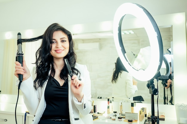 Urocza piękna kobieta fryzjer stylista robi fryzurę i trzyma w ręku lokówkę przed lustrem w studio gabinecie kosmetycznym. koncepcja troski o siebie i miłości własnej