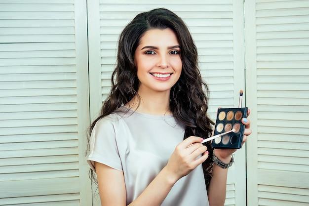 Urocza piękna kobieta visagiste stylistka (wizażystka) trzyma w ręku paletę cieni do powiek i pędzli w studio kosmetycznym. koncepcja pielęgnacji skóry