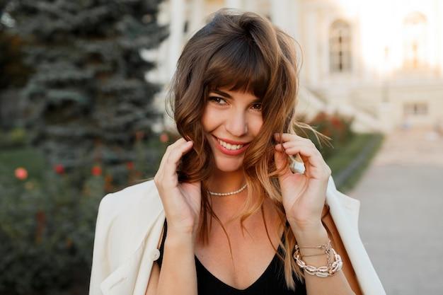 Urocza piękna kobieta z falującą fryzurą, uśmiechnięta, flirtująca, romantyczny nastrój. na sobie białą kurtkę. na wolnym powietrzu. moda na jesień.