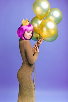 Urocza piękna młoda kobieta w atrakcyjnej modnej sukience z latającymi złotymi balonami. różowa fioletowa fryzura, korona, wesołe emocje, zamknięte oczy, świętowanie.