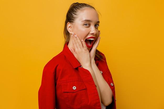 Urocza podekscytowana dziewczyna ubrana w czerwoną kurtkę z czerwonymi ustami trzyma jej czek i bawi się na żółto