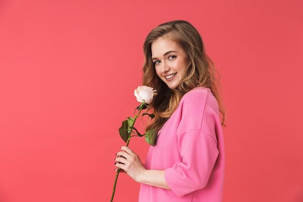Urocza podekscytowana młoda blondynka stojąca odizolowana nad różową ścianą, trzymająca białą różę