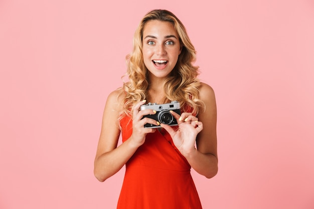 Urocza podekscytowana młoda blondynka ubrana w letnią sukienkę stojącą na białym tle nad różową ścianą, trzymająca aparat portretowy
