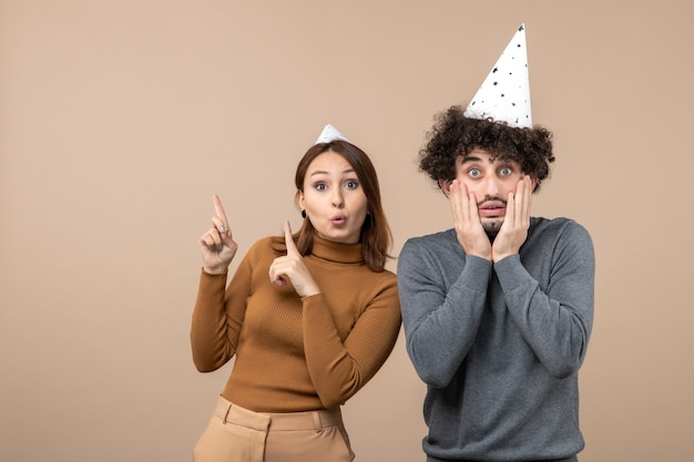 Urocza podekscytowana młoda para nosi kapelusz noworoczny wskazując powyżej i stojącą obok faceta na szarym obrazie