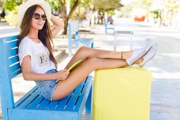 Urocza podróżniczka siedzi na niebieskiej ławce z nogami wyciągniętymi na żółtą walizkę.