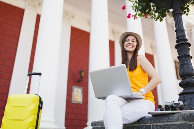 Urocza podróżniczka turystyczna kobieta w ubraniach casual, kapelusz z walizką siedzącą za pomocą pracy na komputerze typu laptop w mieście na świeżym powietrzu. dziewczyna wyjeżdża za granicę na weekendowy wypad. styl życia podróży turystycznej.