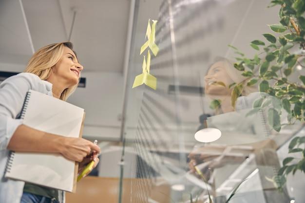 Urocza pracownica patrząca na samoprzylepne papierowe notatki na szklanej ścianie i uśmiechająca się, trzymając spiralny szkicownik