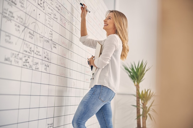 Urocza pracownica pisania na tablicy planisty i uśmiechnięta, trzymając szkicownik