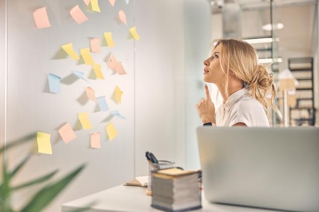 Urocza pracownica siedząca przed ścianą z karteczkami samoprzylepnymi i zastanawiająca się nad najlepszym rozwiązaniem w biurze