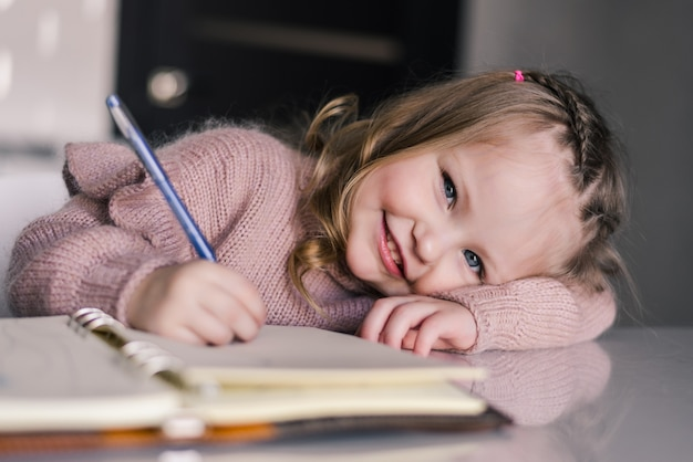 Urocza preschool dziewczyny rysunek z piórem przy stołem