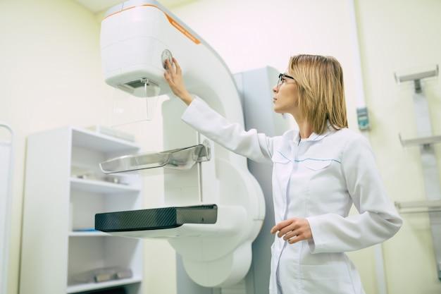 Urocza profesjonalna lekarka pracuje z nowoczesnym systemem mammografii rentgenowskiej w szpitalu lub prywatnej klinice.
