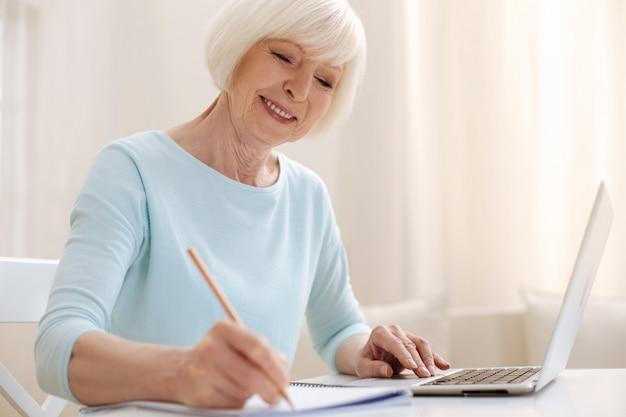 Urocza, przemyślana starsza pani używa laptopa do komunikowania się z kolegami podczas robienia notatek w swoim zeszycie