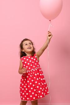 Urocza przepiękna 4-letnia ładna dziewczyna w różowej sukience w kropki raduje się patrząc na różowy balon w podniesionej dłoni, na białym tle na różowym tle z kopią przestrzeni. prawdziwe emocje z dzieciństwa.koncepcje
