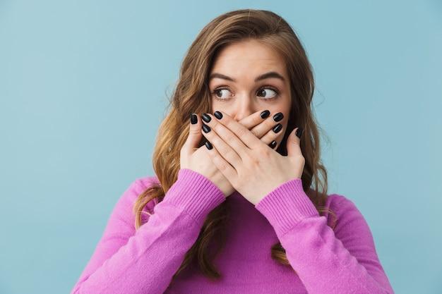 Urocza przestraszona młoda blondynka stojąca odizolowana nad niebieską ścianą, zakrywająca twarz