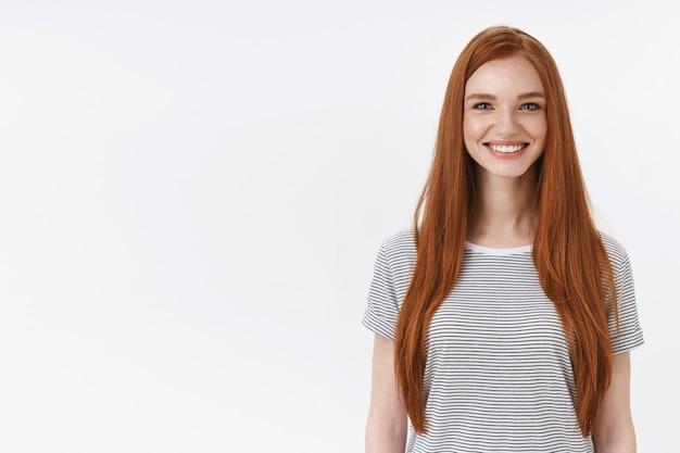 Urocza przyjazna przyjemna ruda dziewczyna studentka uśmiechnięta radośnie kamera spojrzenie podekscytowana uczestnictwo w zajęciach tanecznych nauka nowe hobby stojąca biała ściana zabawna, koncepcja stylu życia