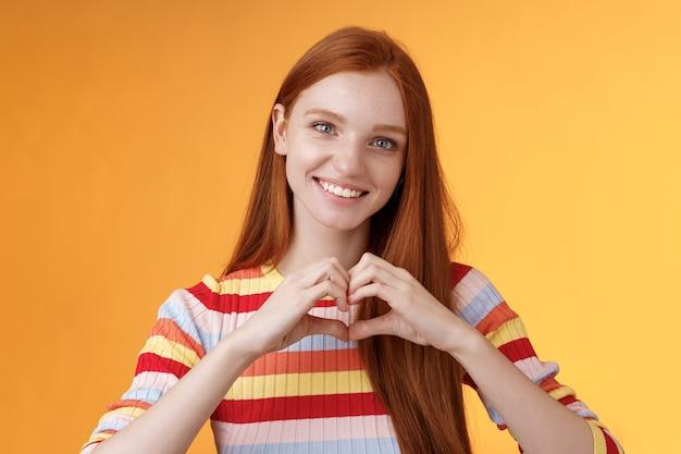 Urocza, przyjaźnie wyglądająca, charyzmatyczna uśmiechnięta ruda dziewczyna wyraża uczucia, miłość i przyjaźń, uśmiechając się, pokazując znak serca na piersi okazując współczucie, wyznając romantyczne uczucia, stojąc na pomarańczowym tle.