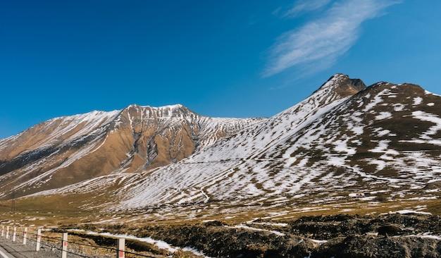 Urocza przyroda, majestatyczne wysokie góry pokryte białym śniegiem pod błękitnym niebem