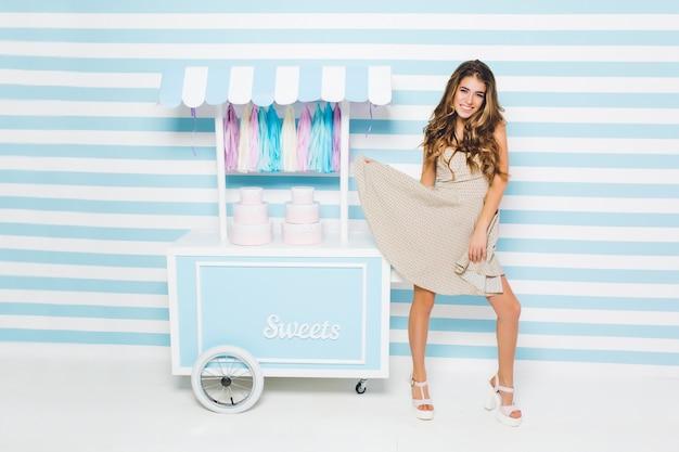 Urocza radosna dziewczyna bawi się swoją stylową sukienką stojącą obok kontuaru ze słodyczami. urocza szczupła młoda kobieta w modnych białych sandałach tańczy na ścianie w paski z uśmiechem.