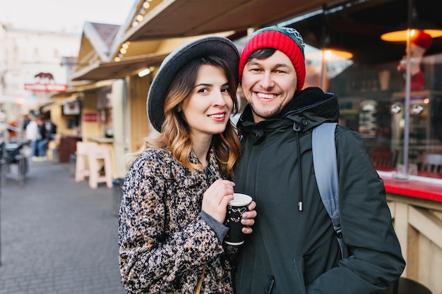 Urocza radosna para relaksująca, przytulająca się na ulicy w czasie świąt bożego narodzenia. prawdziwe emocje miłosne, dobra zabawa, wspólne spędzanie czasu, randkowanie, romantyczny związek, wspólne szczęście.