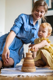 Urocza rodzina montująca drewnianą wieżę ekologiczną maria montessori materiał edukacyjny rozwój
