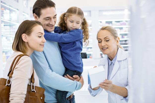 Urocza rodzina słuchająca farmaceutki i patrząc w dół
