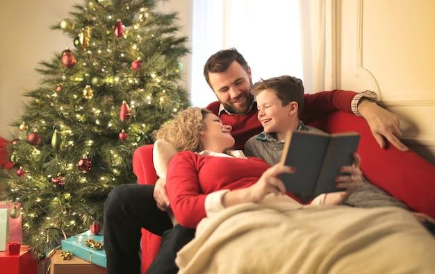 Urocza rodzina spędzająca razem noc bożego narodzenia, czytając książkę siedzącą na kanapie