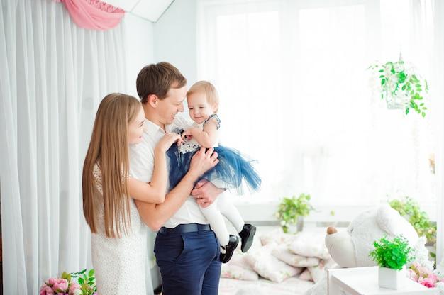 Urocza rodzina uśmiechnięta i śmiejąca się, pozująca do kamery i przytulająca się