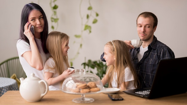 Urocza rodzina w domu z laptopem