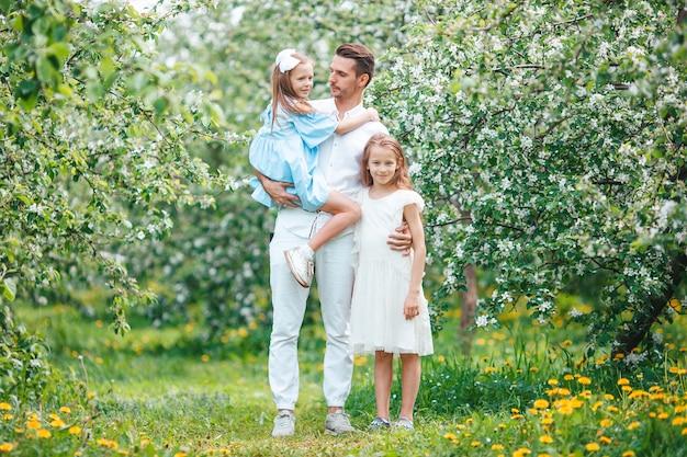 Urocza rodzina w kwitnącym wiśniowym ogrodzie na piękny wiosenny dzień