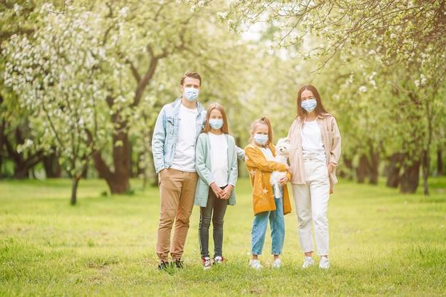 Urocza rodzina w kwitnącym wiśniowym ogrodzie w maskach
