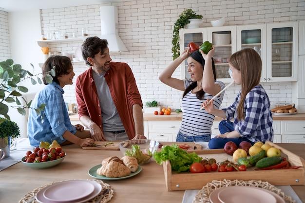Urocza rodzina z dziećmi bawiącymi się razem podczas wspólnego gotowania w kuchni w domu matka tata i dwoje