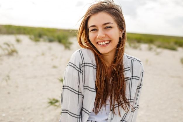 Urocza romantyczna kobieta pozuje na słonecznej plaży, wietrzne włosy, wyraz, letni nastrój.