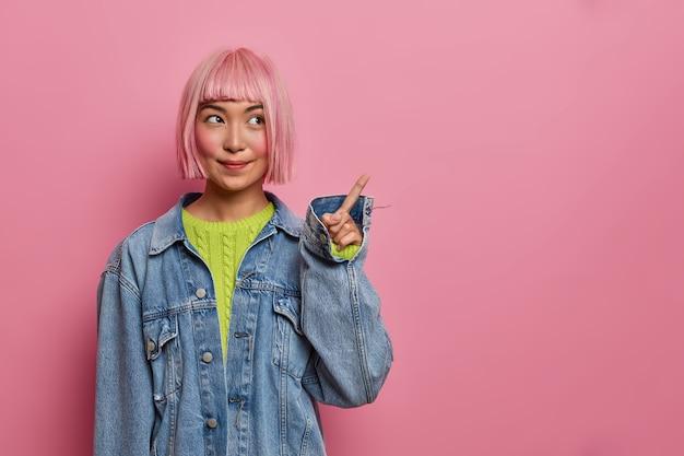 Urocza różowa azjatka z bobowymi włosami, ubrana w za dużą dżinsową kurtkę, wskazuje na miejsce, reklamuje miejsce,