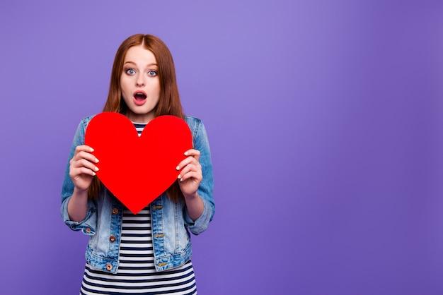 Urocza ruda kobieta pozuje z wielkim papierowym sercem
