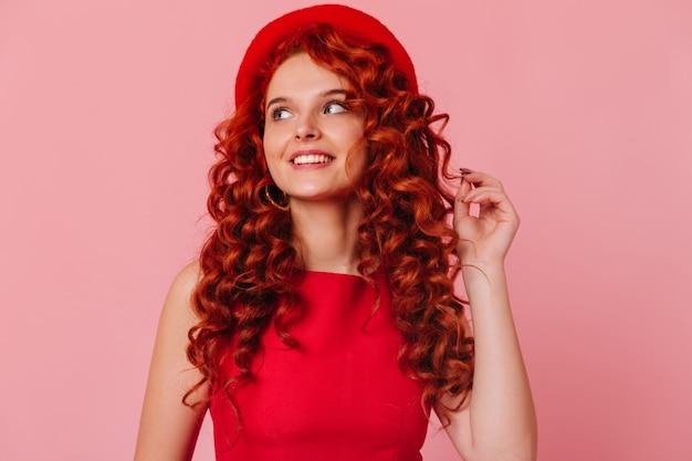 Urocza rudowłosa dziewczyna z uśmiechem odwraca wzrok. kobieta w kapeluszu i czerwonym topie dotyka włosów.