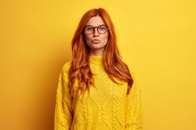 Urocza rudowłosa kobieta ma złożone usta, jakby chciała pocałować kogoś z zalotnym wyrazem twarzy, nosi przezroczyste okulary i dzianinowy sweter.