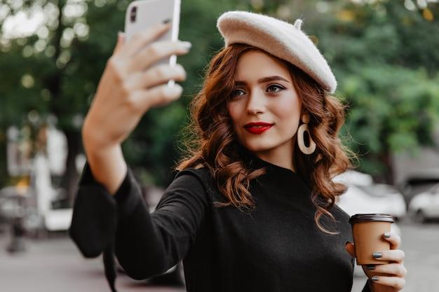 Urocza rudowłosa kobieta w berecie co selfie plenerowe. atrakcyjna pani pije kawę na ulicy.