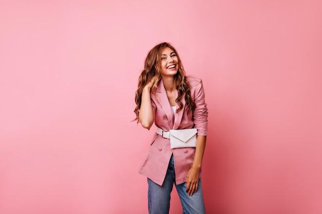 Urocza rudowłosa kobieta w swobodnej kurtce śmiejąca się na różowo. marzycielska młoda dama w dżinsach bawi się kręconymi rudymi włosami.