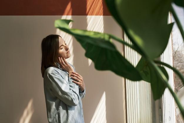 Urocza rudowłosa kobieta z zamkniętymi oczami stoi obok koncepcji samoopieki w oknie