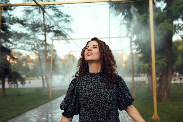 Urocza rudowłosa kręcona dziewczyna raduje się pod wodnym zamgławiaczem w centrum miasta