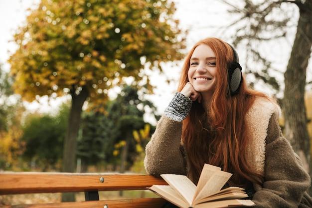 Urocza rudowłosa młoda dziewczyna słucha muzyki z słuchawkami, siedząc na ławce i czytając książkę