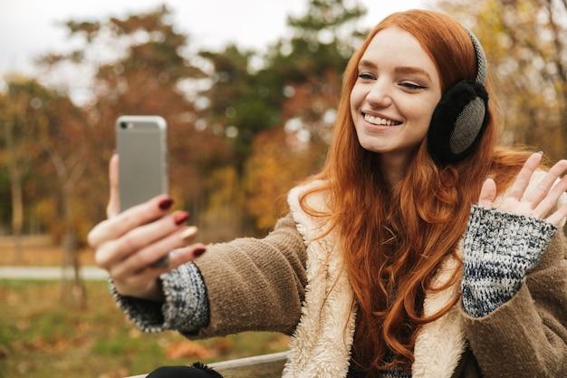 Urocza rudowłosa młoda dziewczyna słucha muzyki z słuchawkami, siedząc na ławce, robiąc selfie
