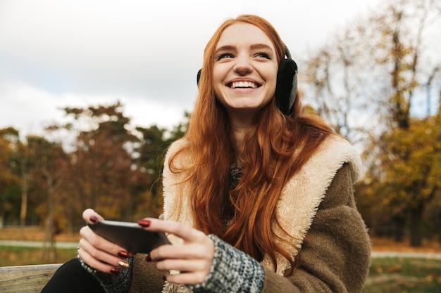 Urocza rudowłosa młoda dziewczyna, słuchając muzyki w słuchawkach, siedząc na ławce przy użyciu telefonu komórkowego