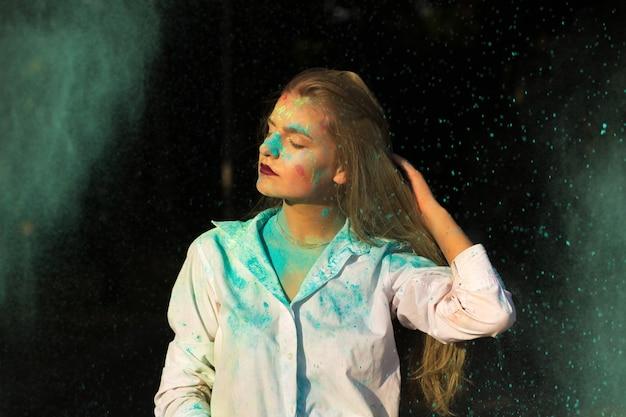 Urocza rudowłosa młoda kobieta w białej koszuli pozuje z eksplodującą suchą farbą holi