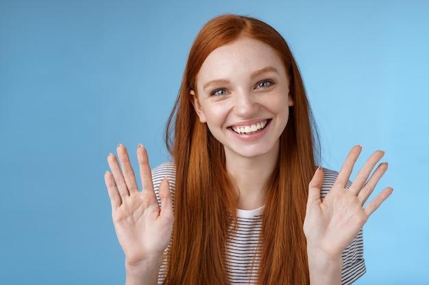 Urocza rudowłosa starsza siostra żegna rodzeństwo, uśmiechnięte wesoło, machające uniesione dłonie pokazują dziesięć palców, uśmiechając się radośnie, wyglądają na beztroskiego zrelaksowanego, rozmawiającego niedbale na niebieskim tle.