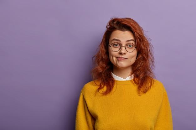 Urocza rudowłosa wonan zaciska usta, ma poważny wyraz twarzy, zdrową skórę, nosi okulary optyczne, żółty sweter na co dzień